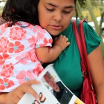 Laura Torres holds her daughter as she speaks to reporters at an immigration rally. - 19 August 2013